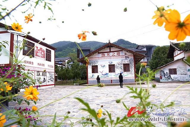 近日,记者走进黔江区冯家街道中坝社区1组境内的碗厂坪美丽庭院,鲜花、果树、彩色绘画妆点着农家院落.图片